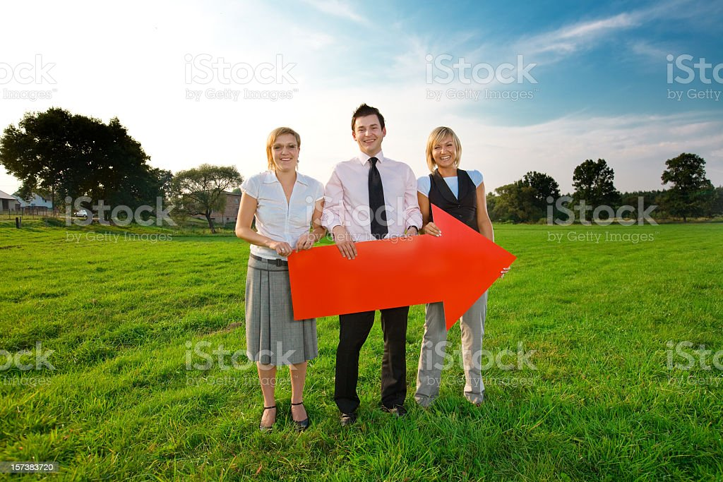Three people holding red arrow royalty-free stock photo