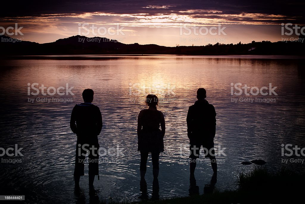 Three people in lake Hopfen royalty-free stock photo