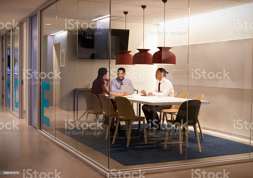 Three people in meeting cubicle at a big corporate business stock photo