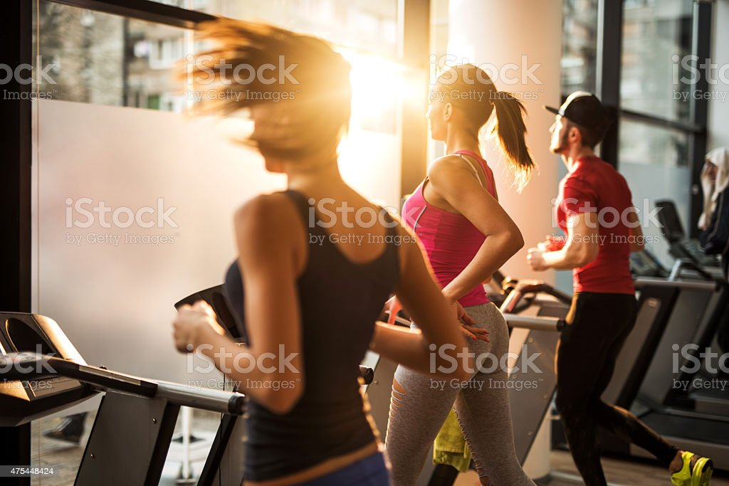 Three people jogging on treadmills in a gym. stock photo