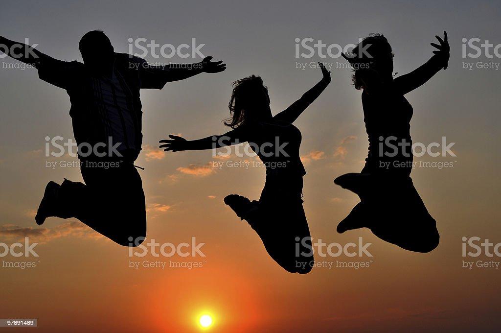 Three people jumping at sunset royalty-free stock photo