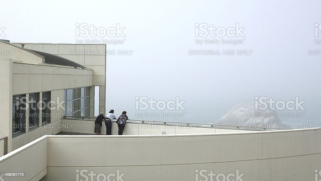 Three people look out to sea royalty-free stock photo