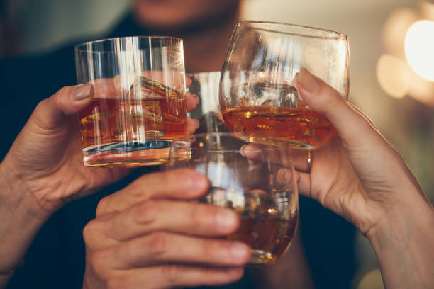 three people makes a toast with whiskey - whiskey stock photos and pictures