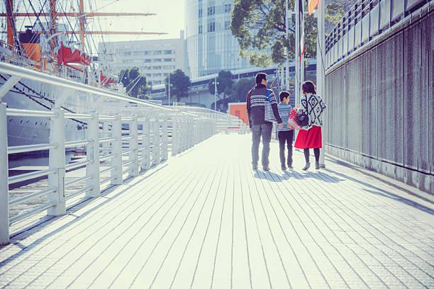 Three people of family walking bayside walk ストックフォト
