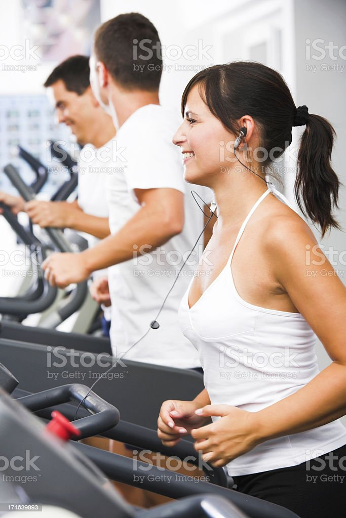 Three people on a treadmill running at a gym royalty-free stock photo