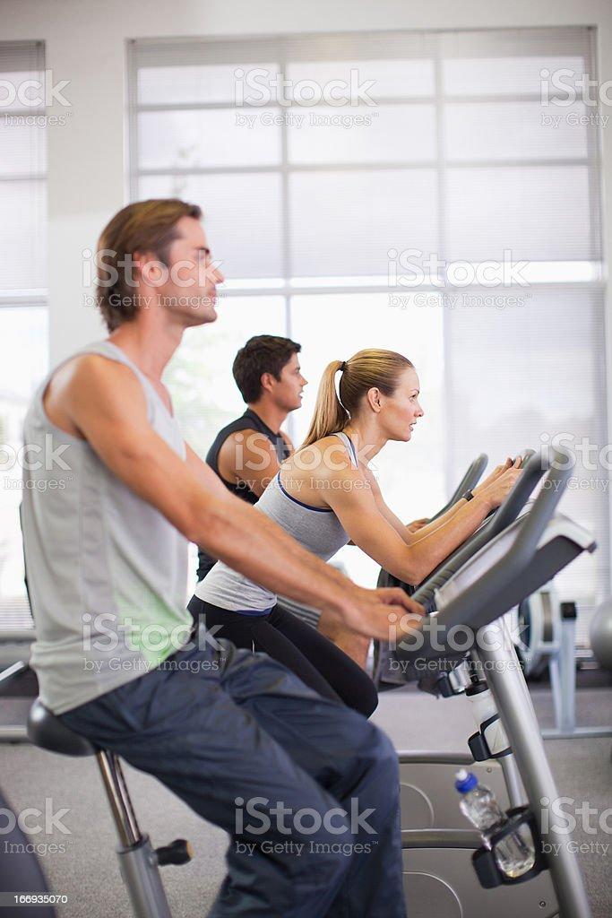 Three people on exercise bikes in gymnasium royalty-free stock photo