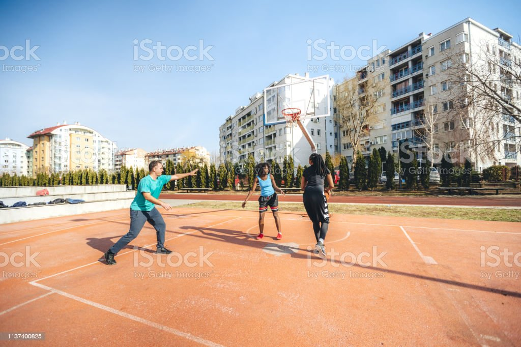 Ethnically diverse group of people are playing basketball on the...