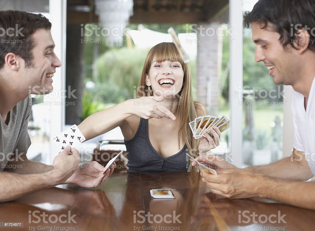 Three people playing cards at table and smiling stock photo