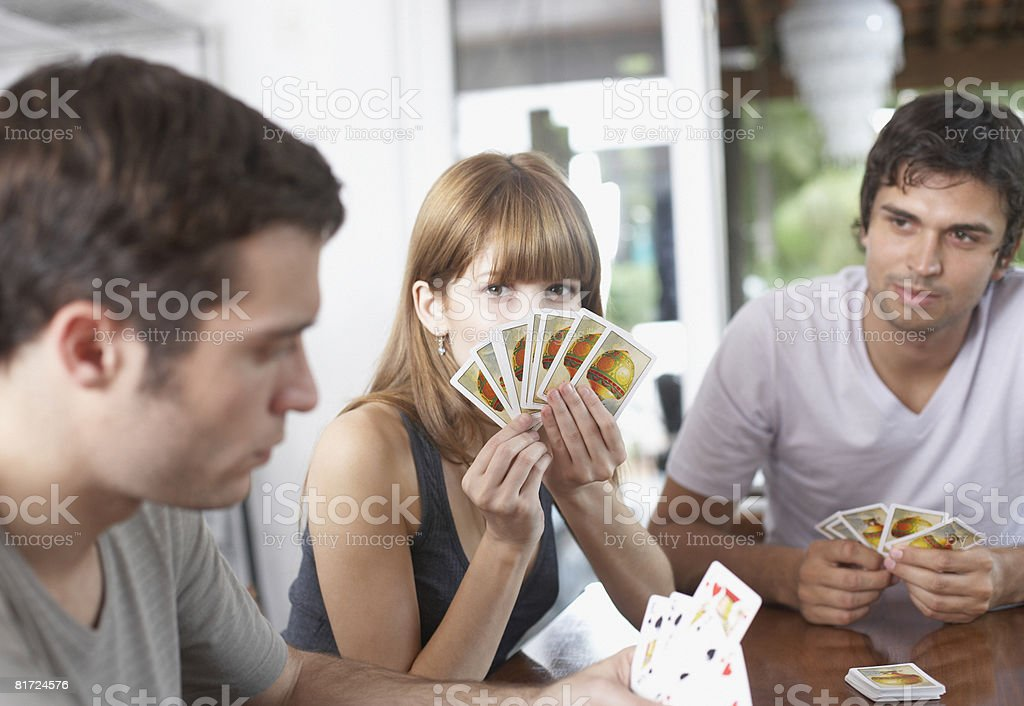 Three people playing cards at table royalty-free stock photo