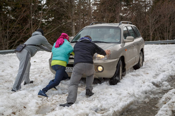 Three people push a car that is stuck in deep snow stock photo