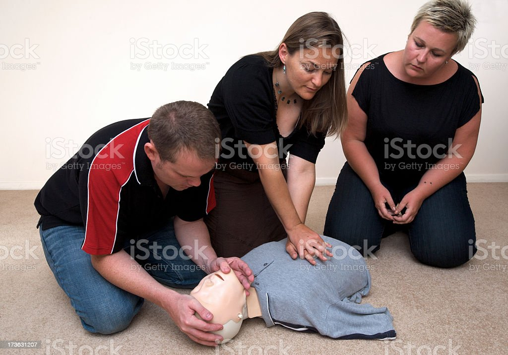 3 people practice CPR on a dummy