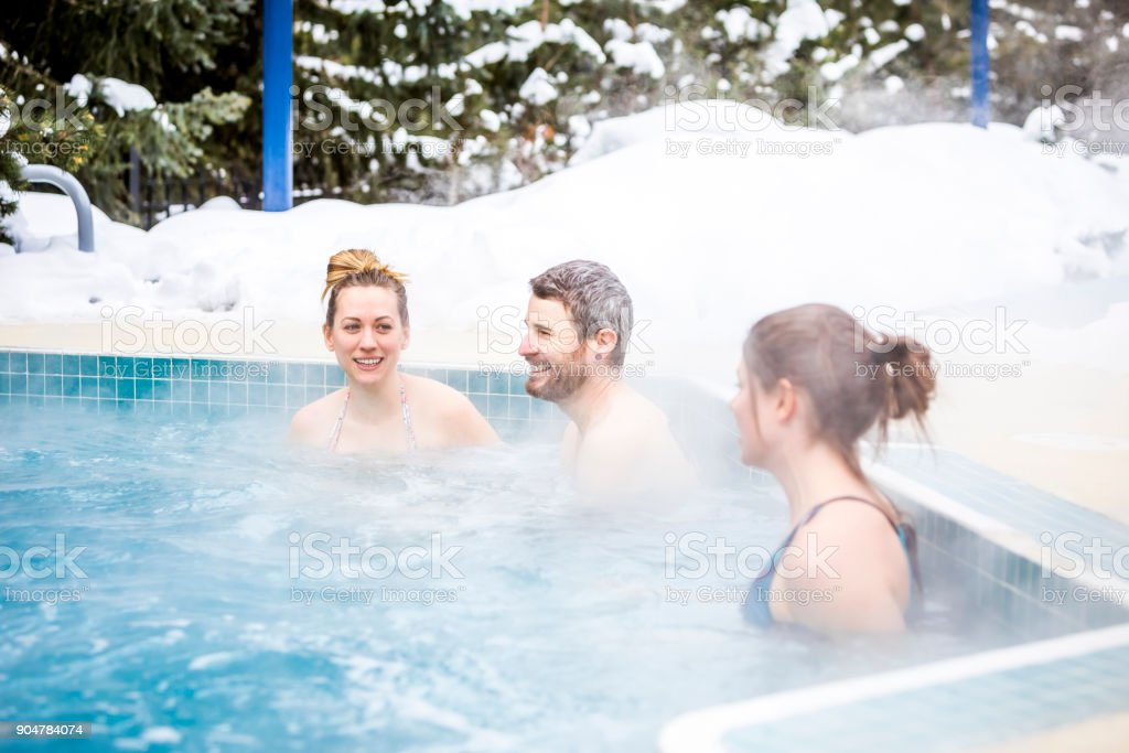 Three people resting in hot tub. stock photo