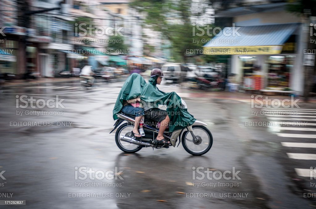 Three People Riding Through A Storm In Vietnam stock photo