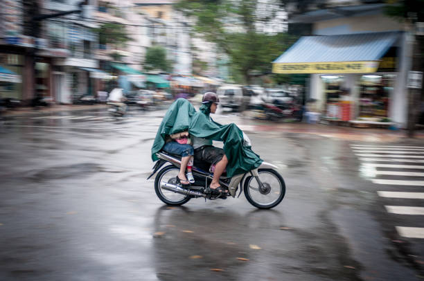 three people riding through a storm in vietnam - motorbike, umbrella stock photos and pictures