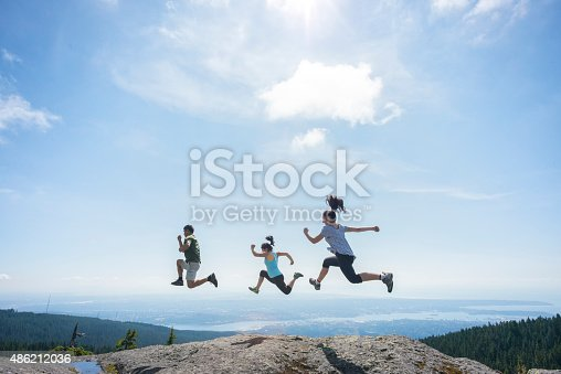903015102 istock photo Three People Running and Jumping on Mountain Top, Cliff Edge 486212036