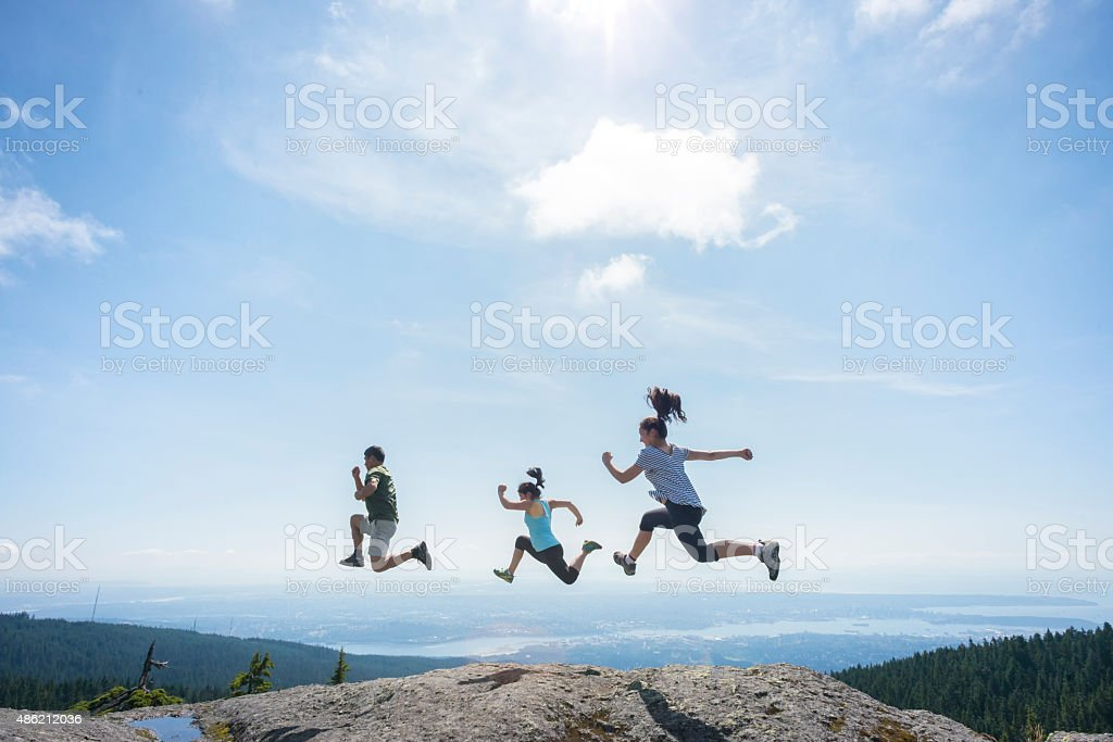Three People Running and Jumping on Mountain Top, Cliff Edge stock photo
