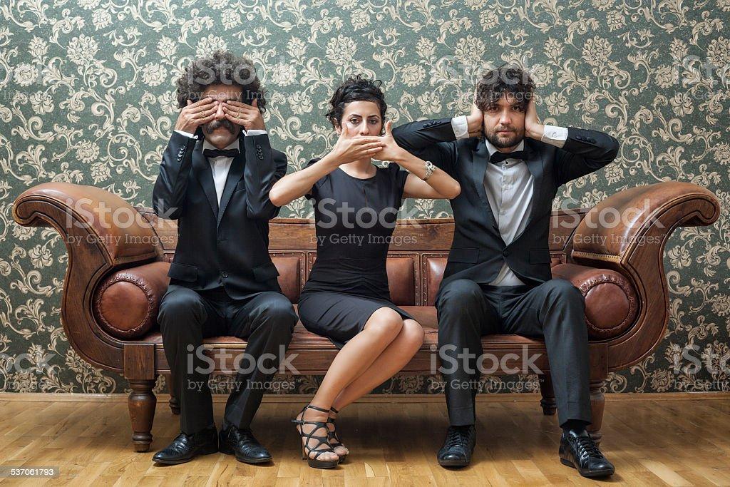 Three people sit together on a sofa like the three monkeys. stock photo