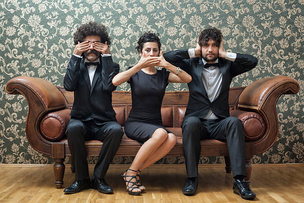 Three people sit together on a sofa like the three monkeys. Three monkeys on sofa hear no evil stock pictures, royalty-free photos & images