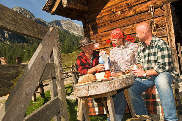 Three people sitting in front of alpine hut stock photo