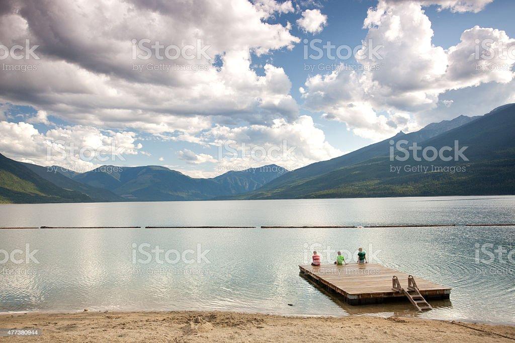 Three People Sitting on Dock at Mountain Lake stock photo