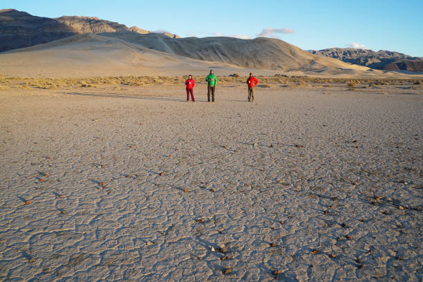 Three people stand on the desert playa in front of Eureka Dunes stock photo