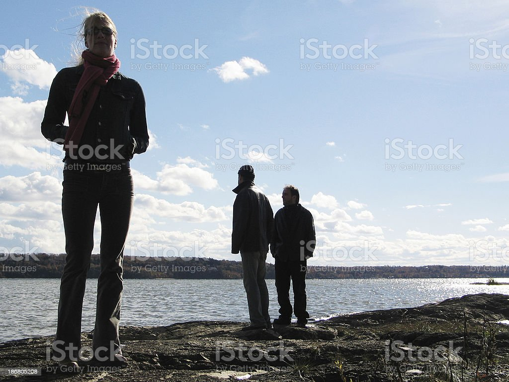 Three people standing by the bay royalty-free stock photo