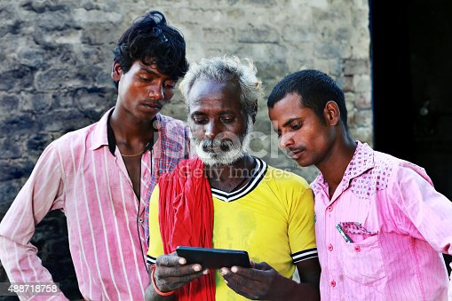 Three Poor People Standing Holding Mobile Phone Near Old Brick Wall & Looking inside the Mobile Phone Screen
