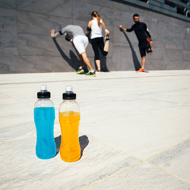 Three people stretching with blue and orange drinks stock photo