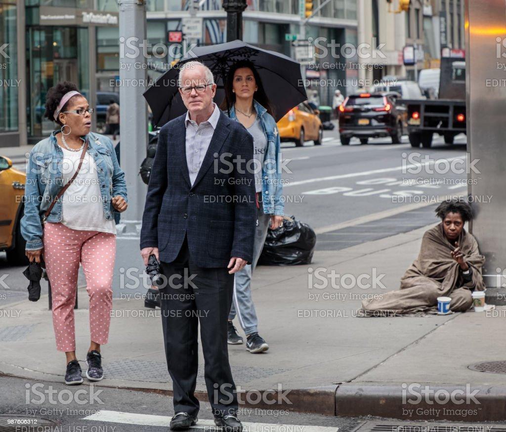 Drei Menschen warten auf die Ampel und man sitzt auf dem Bürgersteig – Foto
