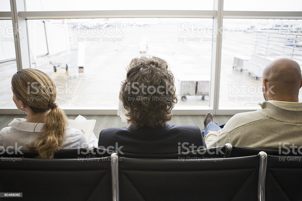 Three people waiting in an airport terminal royalty-free stock photo