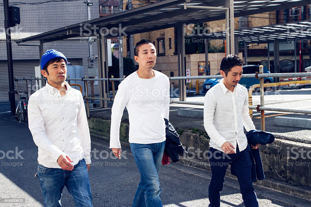 Three people walking a road at a town in Tokyo stock photo