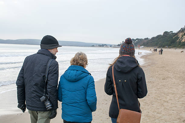 Three people walking along the beach on a winters day stock photo