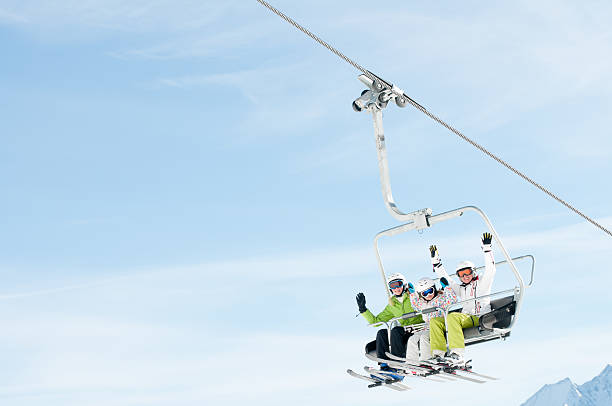 Three people with arms raised up on a ski lift  stock photo