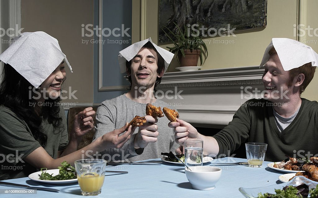 Three people with napkins on heads, at dining table royalty-free stock photo