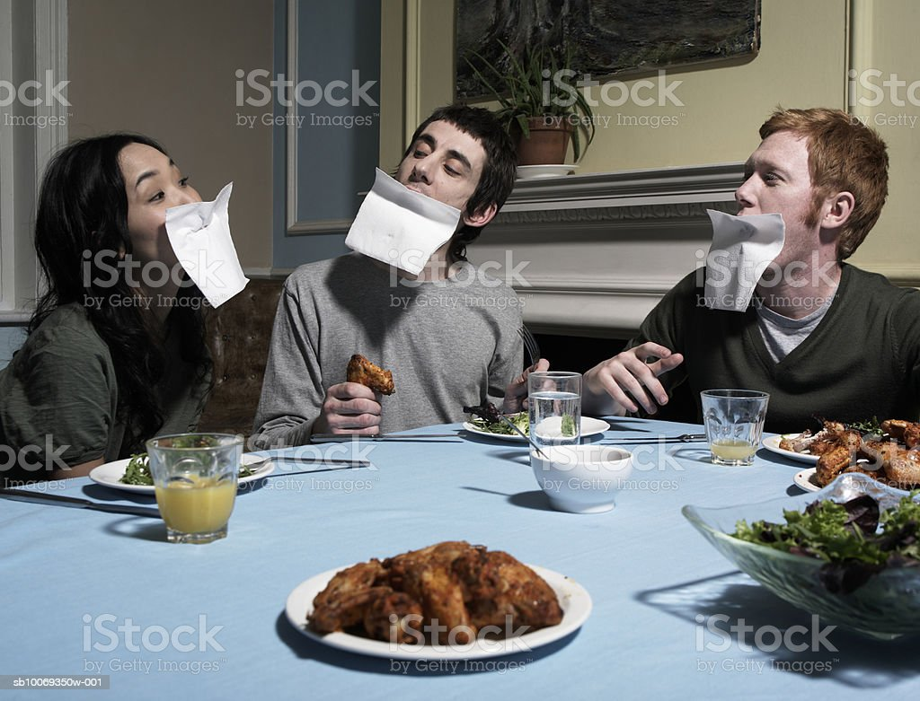 Three people with napkins over faces, at dining table royalty-free stock photo