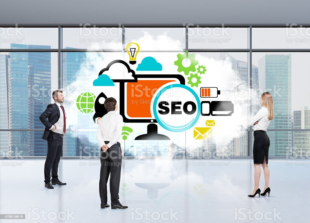 Three persons in an office are tackling with SEO. stock photo