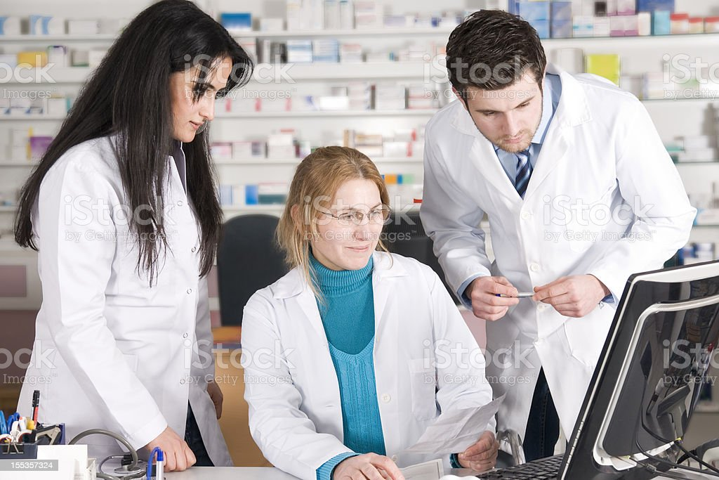 Three pharmaceutical professionals on the computer royalty-free stock photo
