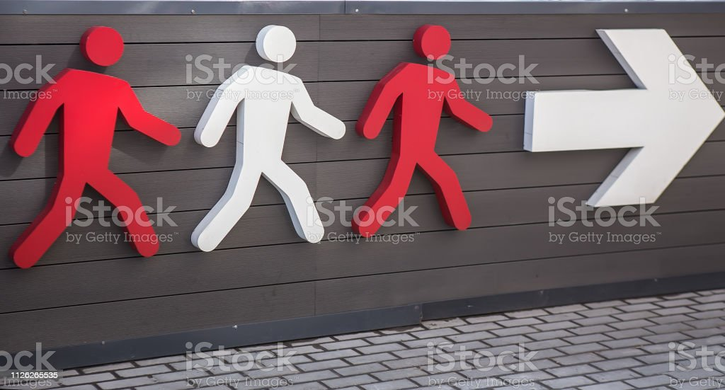 Drei Piktogramme der Person zu Fuß in Richtung der weißen Pfeil. – Foto