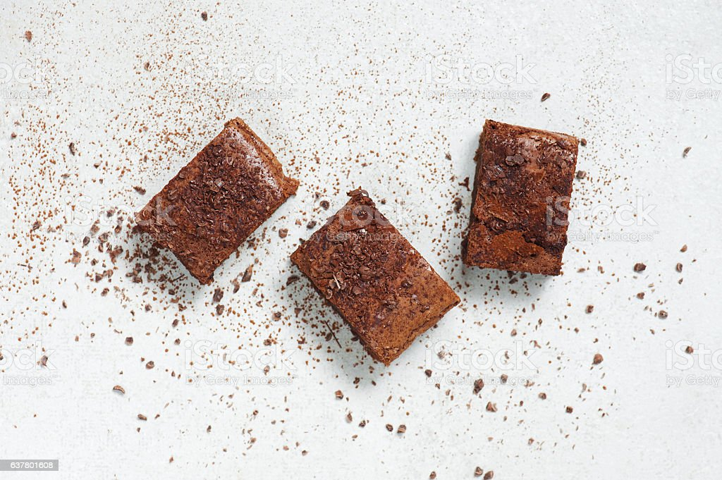 Three pieces of brownie topped with chocolate chips and cocoa – Foto