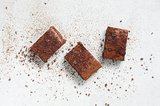 Three pieces of brownie topped with chocolate chips and cocoa - foto stock