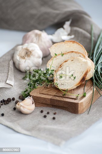Three pieces of French baguette on a wooden board and fresh herbs.