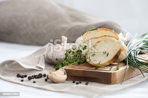 Three pieces of fresh French baguette on a wooden board and fresh herbs.