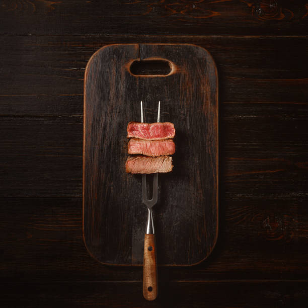 three pieces of meat on a fork for meat - raw steak imagens e fotografias de stock