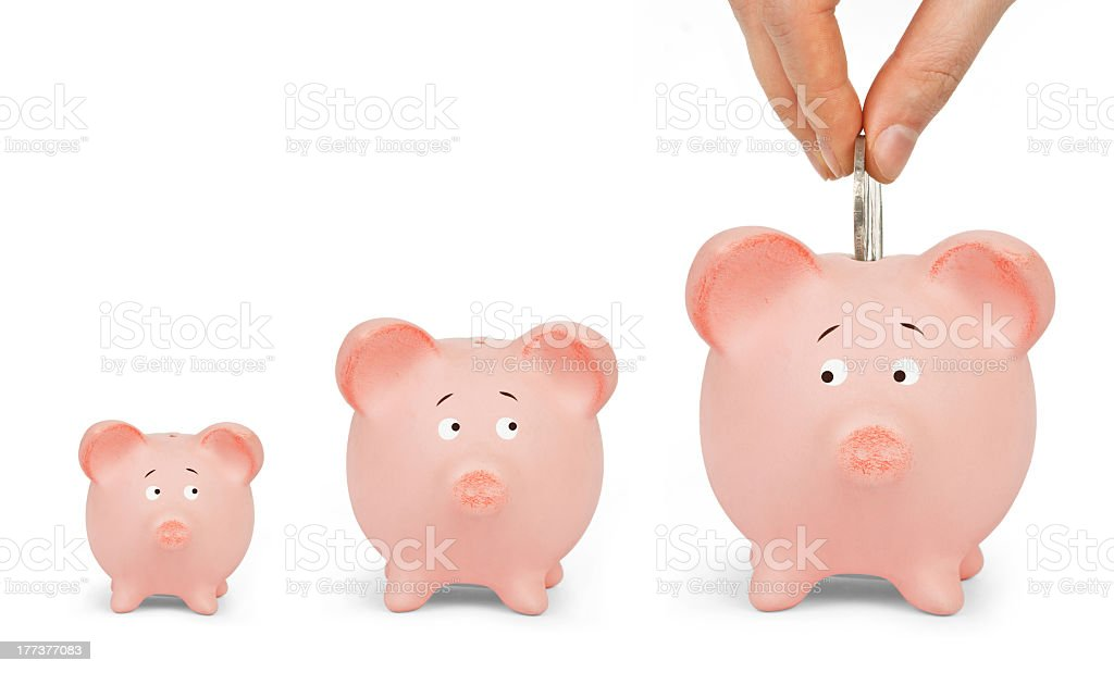 Three piggy banks, hand dropping coin into largest one royalty-free stock photo