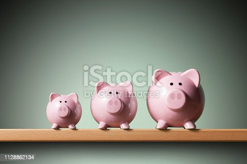 Three piggy banks on the shelf. Small, medium and large.