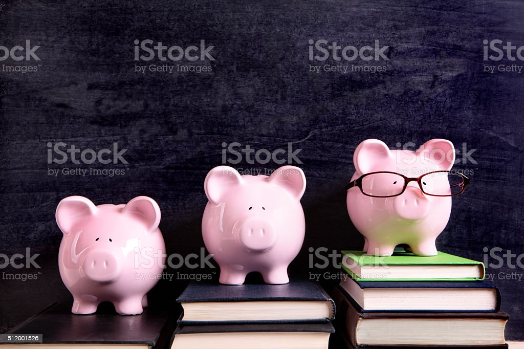 Three piggy banks with blackboard stock photo