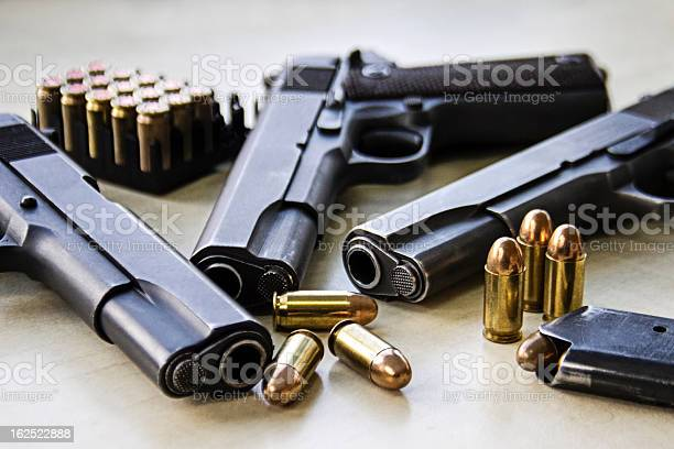 Three pistols laying on table with bullets