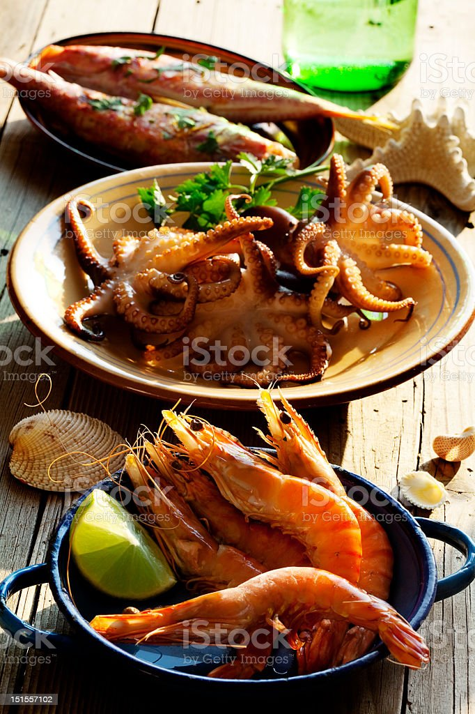 Three plates of seafood including fresh herbs stock photo