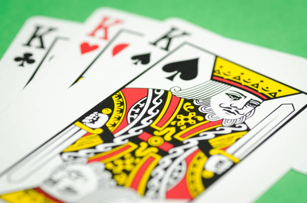 three playing cards on green background