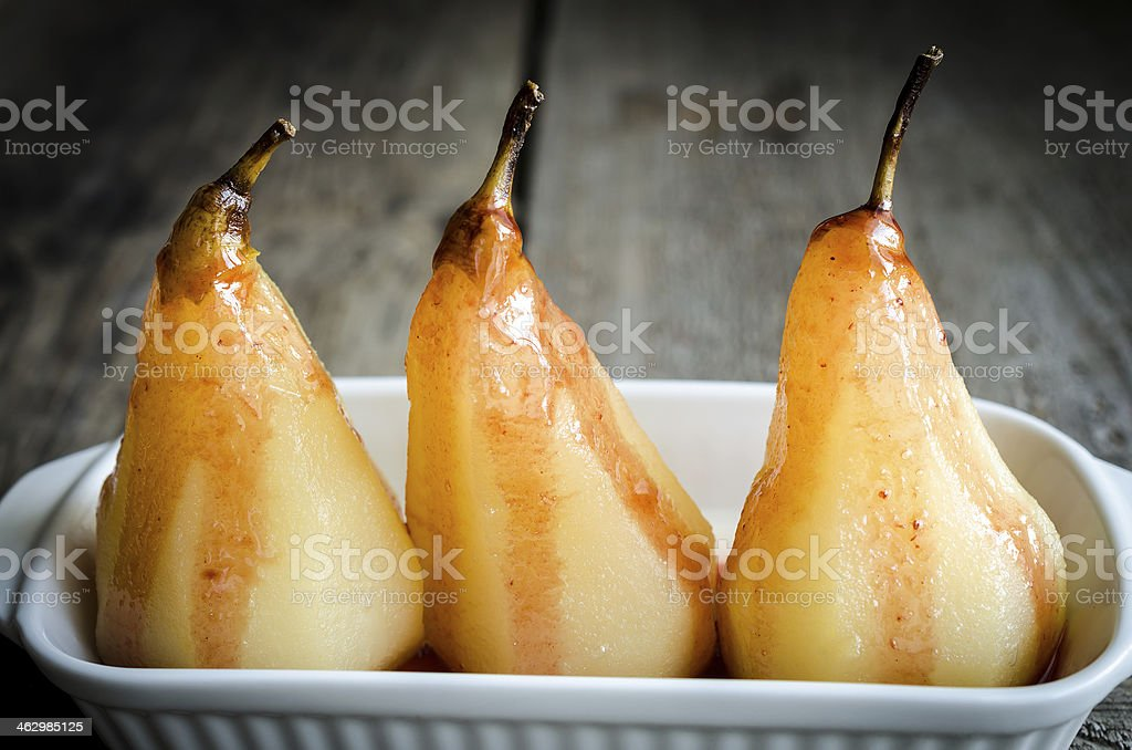 Three poached pears presented in a white serving dish stock photo